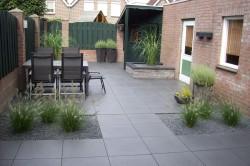Strakke achtertuin met keramische tegels